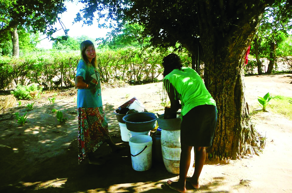 Alicia Krawchuk (left) washes dishes in Africa. Courtesy of Mariah Bargan.