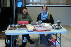 Carly Schmidt and teammate Victoria Pappas selling baked goods for the girls' basketball team. They will be in the Odeon building lobby through Thursday, Oct. 23. Photo by Kyle Morrisson