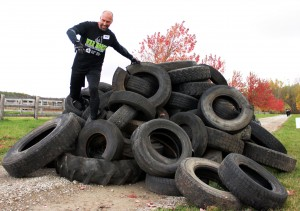 Dan Leal, of the Mud Warriors team, hops over the tire pile, the final obstacle of the War Horse Warrior Challenge Mud Run, which took place at the Southern Cross Equestrian Academy on Saturday morning. Photo by Jacob Dearlove