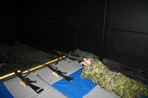 Sgt. Chris Gagen demonstrates shooting a rifle in the Small Arms Training room. Photo by Marissa White