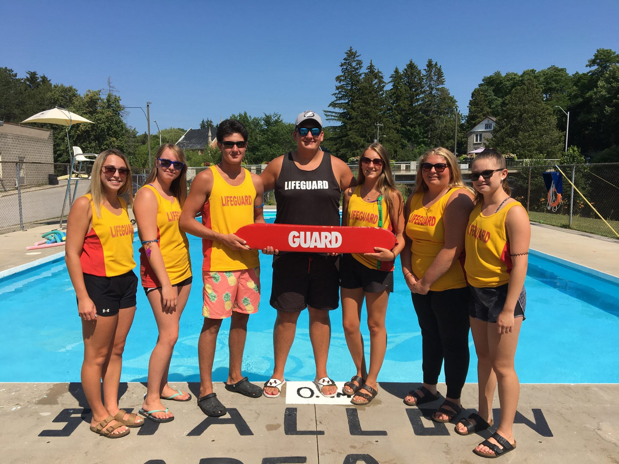 A group of lifeguards smile for the camera in front of an outdoor pool.