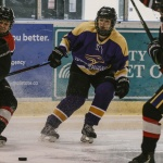 Laurier Brantford women's hockey player has her eyes on the puck between her opponents.