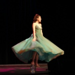 Woman twirls in a green gown onstage at Fashion for Freedom's annual fashion show.