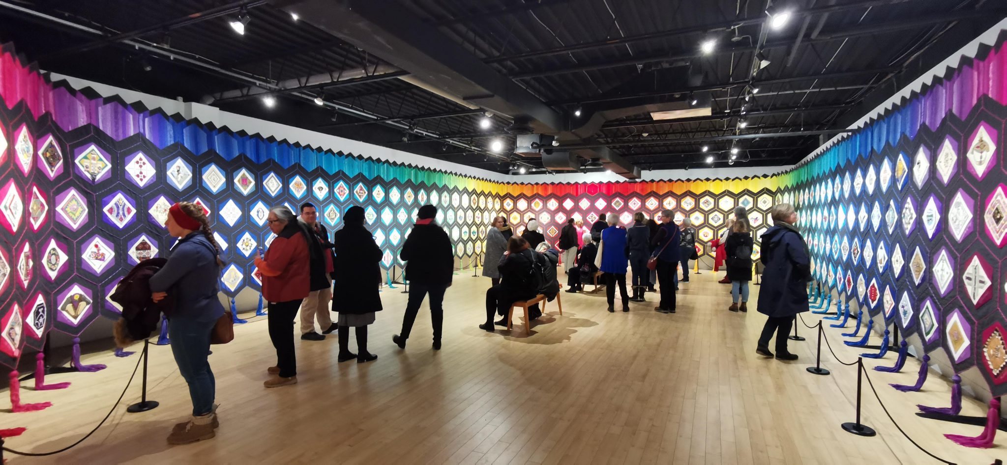 People gather to observe a rainbow-coloured installation spanning wall-to-wall.