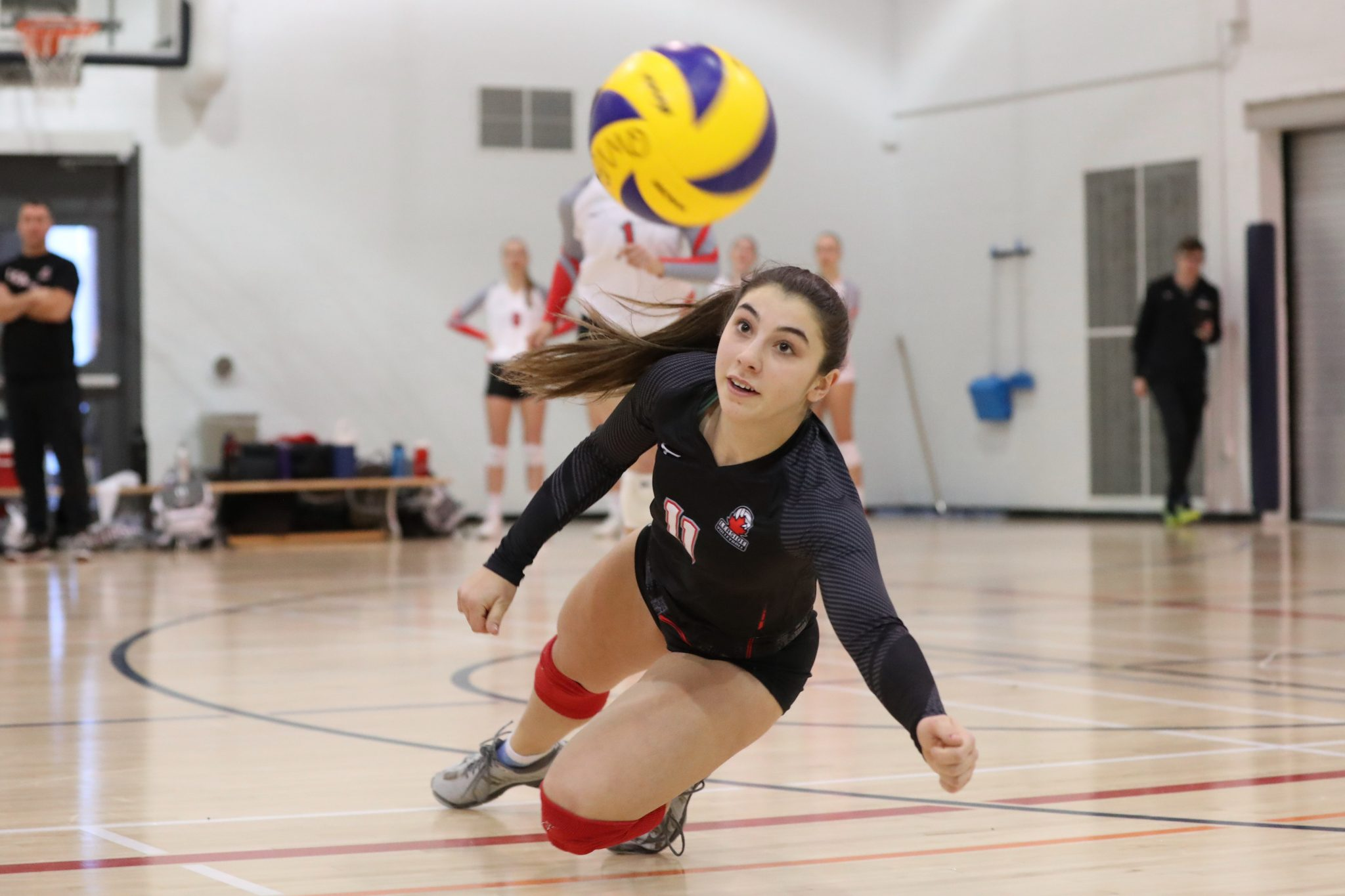 Female athlete dives for a volleyball