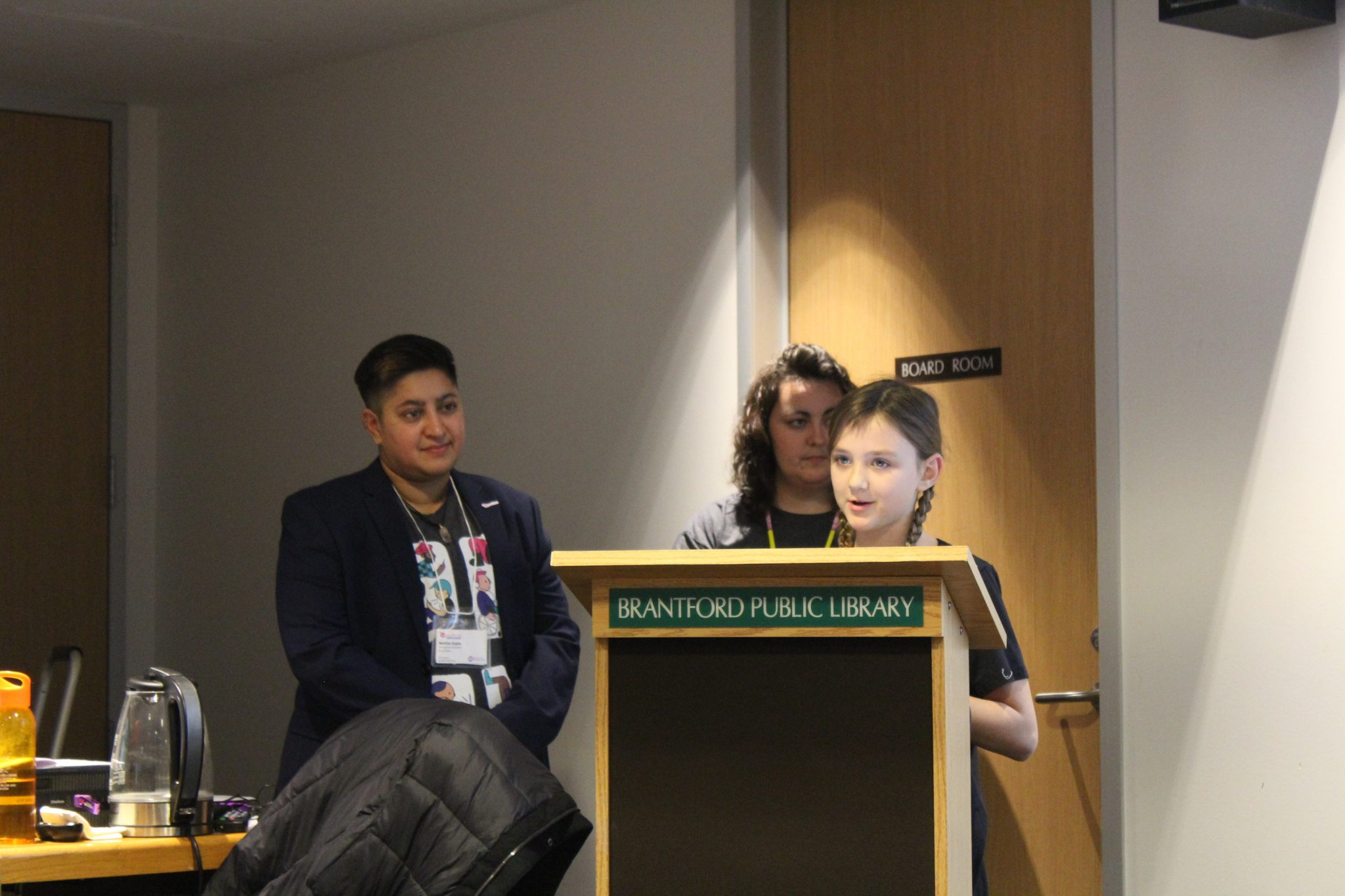 Young youth ambassador speaks at a podium at the Youthline event.