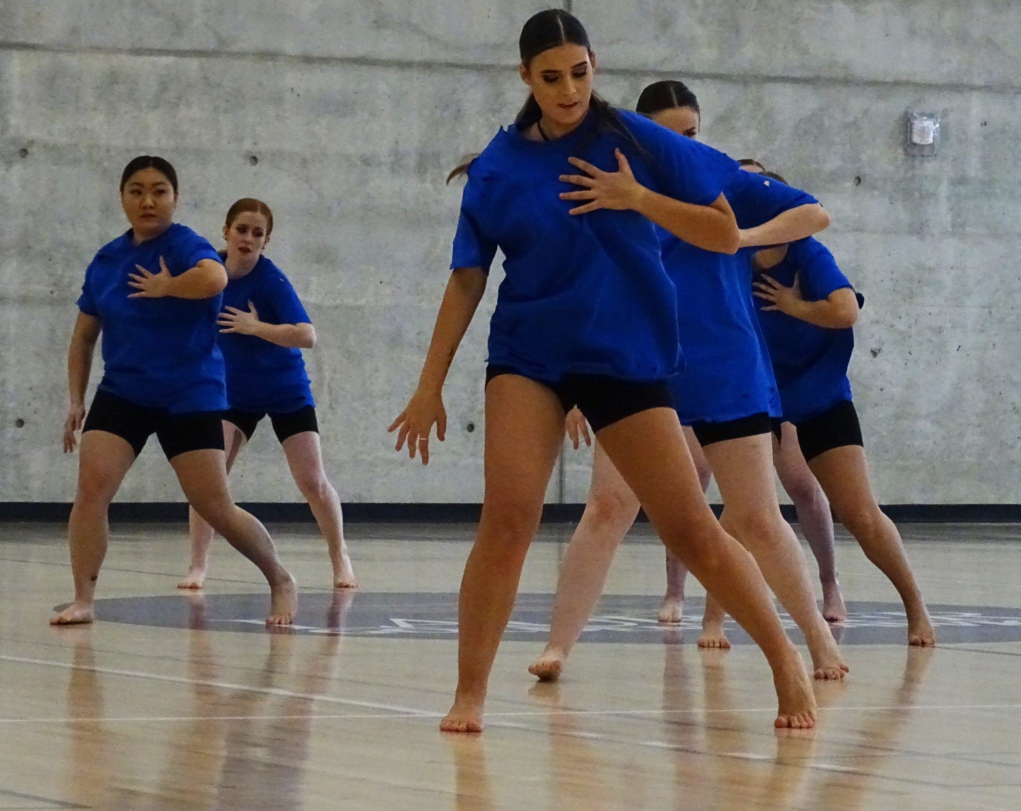 Female dancers in blue t-shirts perform in synchrony.