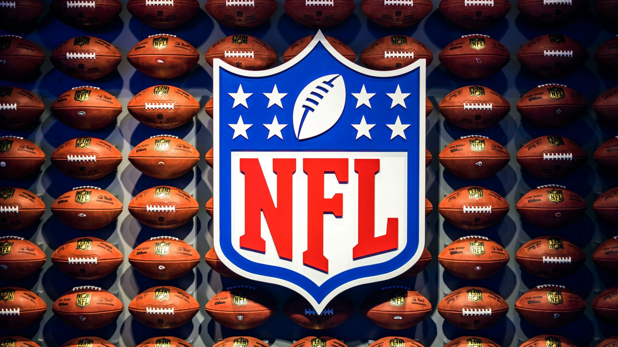 NFL logo surrounded by footballs.