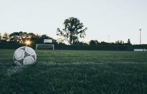 A soccer ball sitting in an empty field.