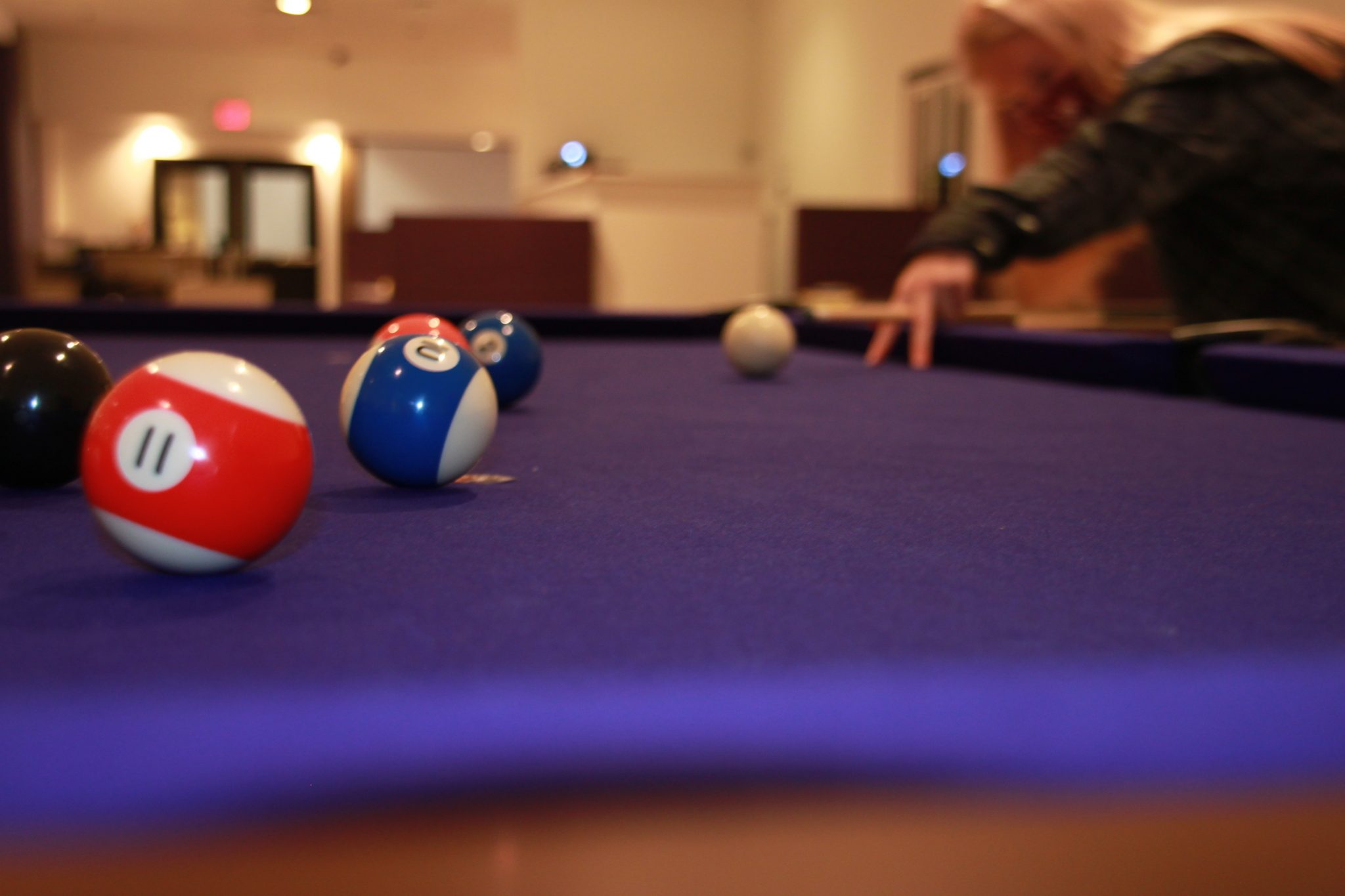 A person setting up their shot in a game of pool.