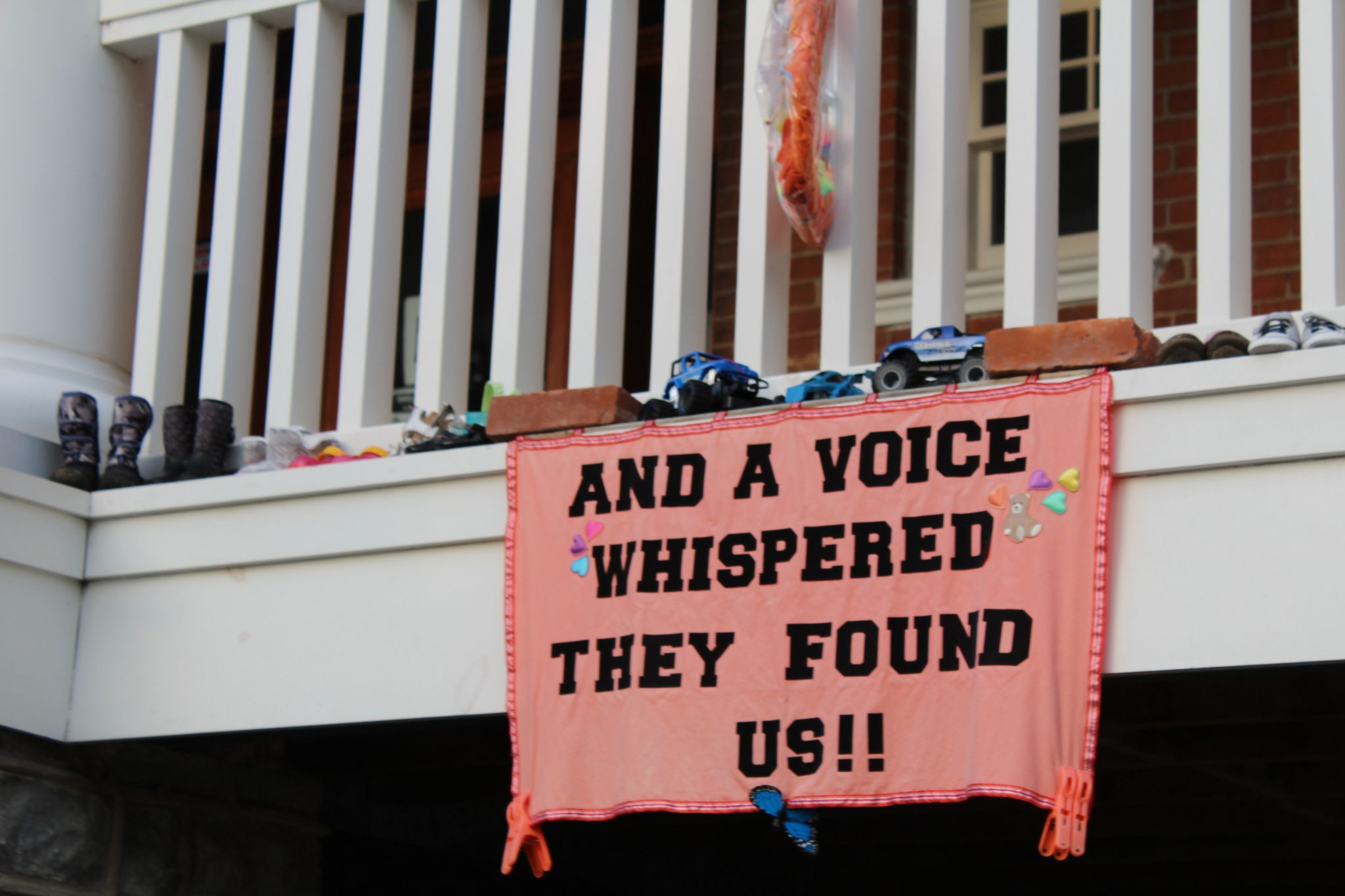 """An orange sign reads """"And a voice whispered 'they found us!!'"""""""