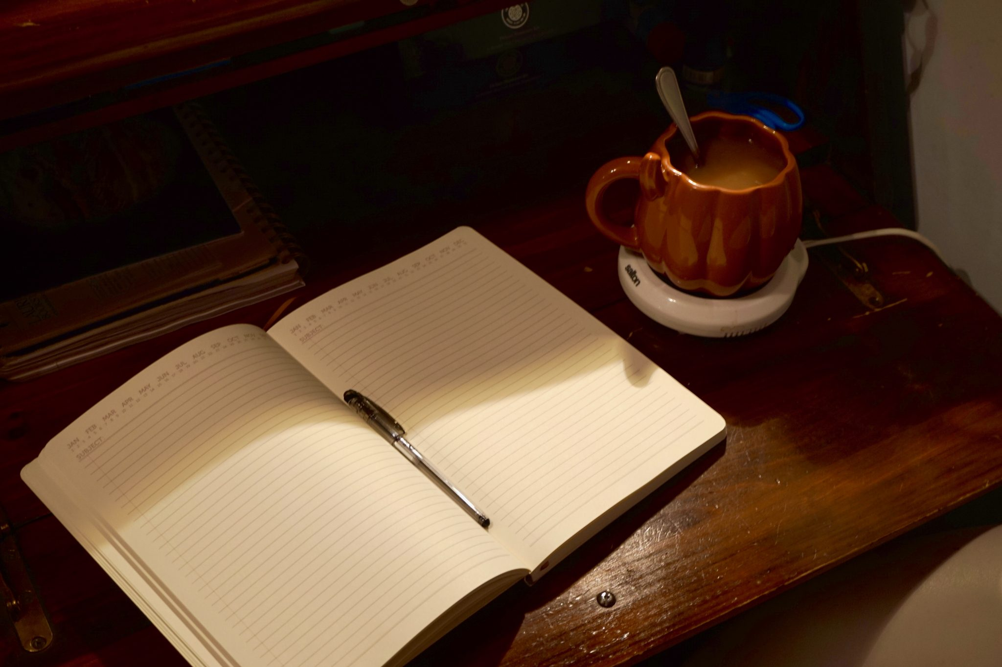 Notebook and pen on a table with a mug of tea.