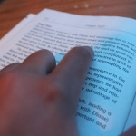 A finger tracing words in a book
